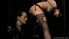 She's tied up and her mistress is playing with her pussy through bars