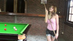 Busty Kate makes some shots on the pool table as she strips and poses