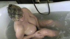 Buxom blonde bombshell Bea Flora plays with her monstrous tits in the bathtub