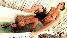 Sexy lesbians in the bath play with their feet and do some pussy rubbing