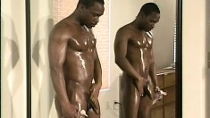 A naughty dude oils his hot black body before stroking his pole