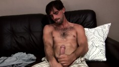 Joe Parker spreads his body across the sofa and makes himself cum hard